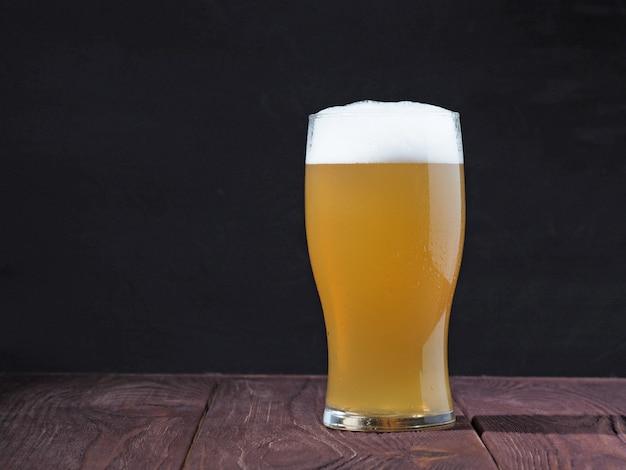 Un vaso humeante de cerveza sin filtrar con una tapa espumosa sobre una mesa de madera