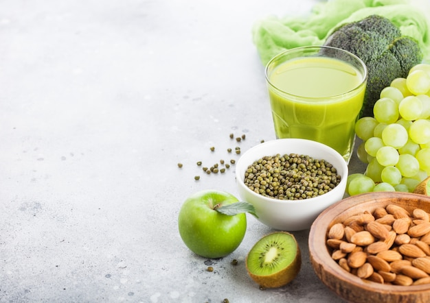 Vaso de jugo de batido fresco frutas y verduras en tonos verdes orgánicos en la cocina de piedra. con almendras y frijoles mung en un tazón.