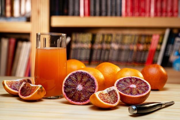 Vaso de jugo, cuchillo y naranjas rojas cortadas en una mesa de madera clara