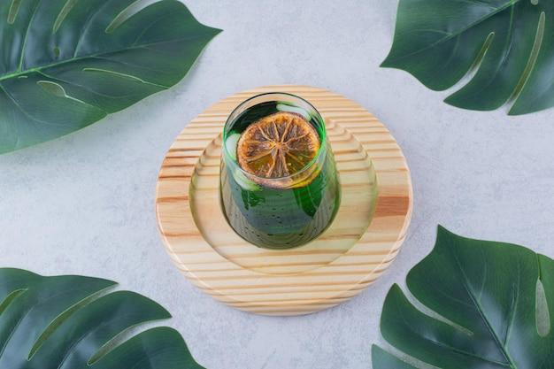Vaso de jugo de estragón en placa de madera. foto de alta calidad