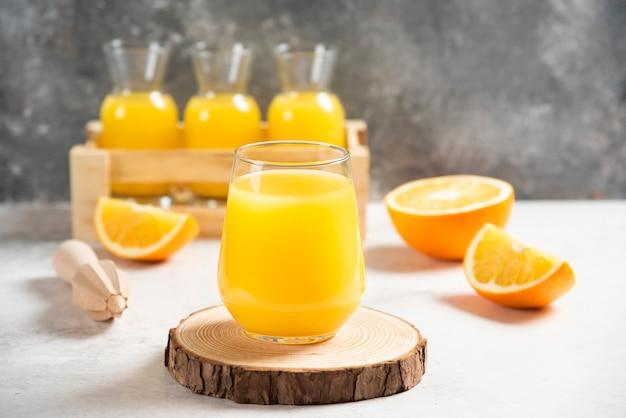 Un vaso de jugo fresco con rodajas de naranja.