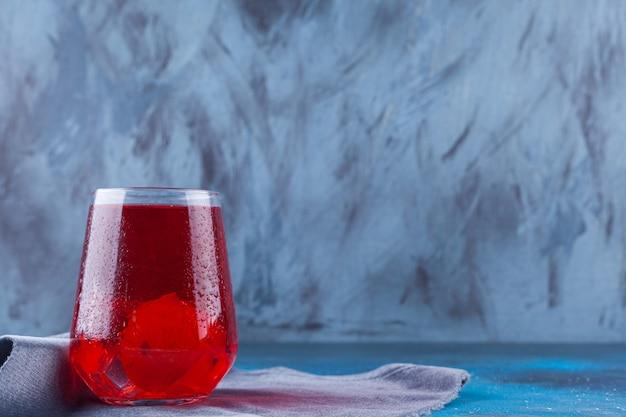 Un vaso de jugo de fruta con cubitos de hielo colocados sobre una superficie de tela de saco