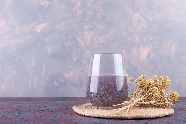 Vaso de jugo de fruta morada con flor seca colocada sobre un fondo oscuro.