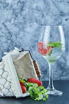 Un vaso de jugo con frutas enteras en el interior y una canasta de fresas en la superficie azul