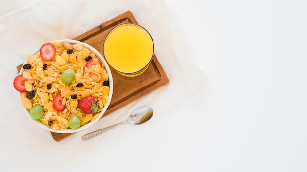 Vaso de jugo de mango y copos de maíz con frutas en un tazón blanco en una tabla de cortar contra un fondo blanco