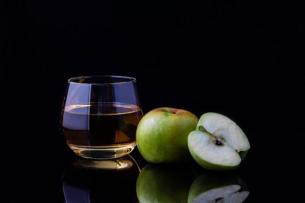 Un vaso de jugo de manzana y una manzana en rodajas sobre un fondo oscuro.