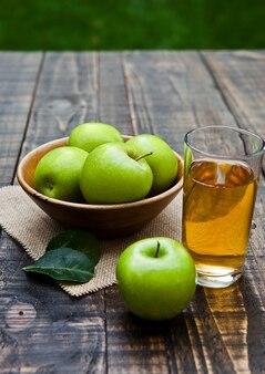 Vaso de jugo de manzana con manzanas verdes saludables en un tazón de madera. afuera en el jardín
