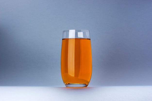 Vaso de jugo de manzana y uva aislado sobre fondo blanco.