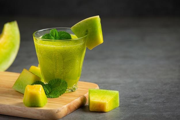 Vaso de jugo de melón puesto sobre tabla de cortar de madera