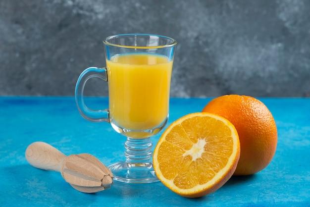 Un vaso de jugo de naranja en azul.