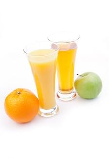 Vaso de jugo de naranja cerca de un vaso de jugo de manzana