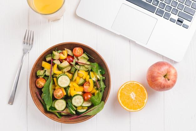 Vaso de jugo; naranja cítrica; ensalada de manzana y verduras mixtas con tenedor y laptop en el escritorio de madera blanco