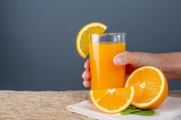 Vaso de jugo de naranja colocado en la madera.