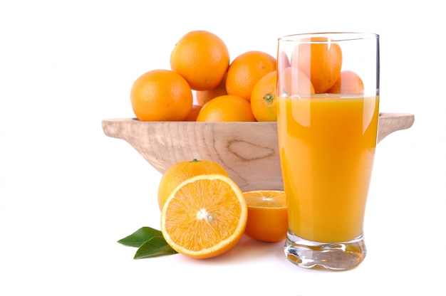 Vaso de jugo de naranja frente a un tazón de madera lleno de frutas