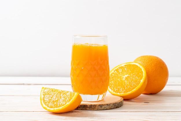 Vaso de jugo de naranja fresco en madera