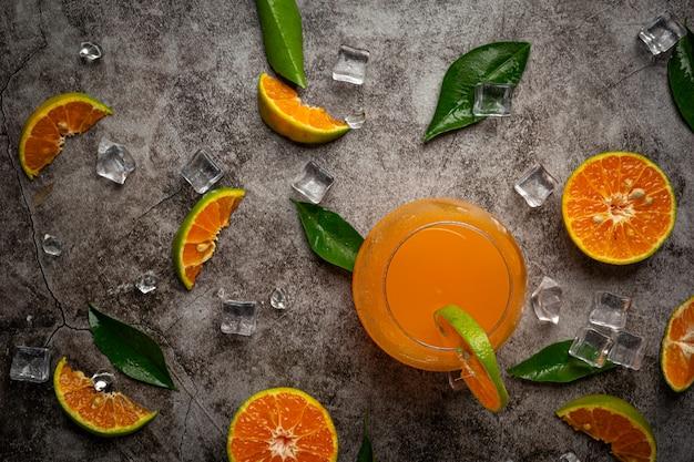 Un vaso de jugo de naranja y fruta fresca en el piso con cubitos de hielo.