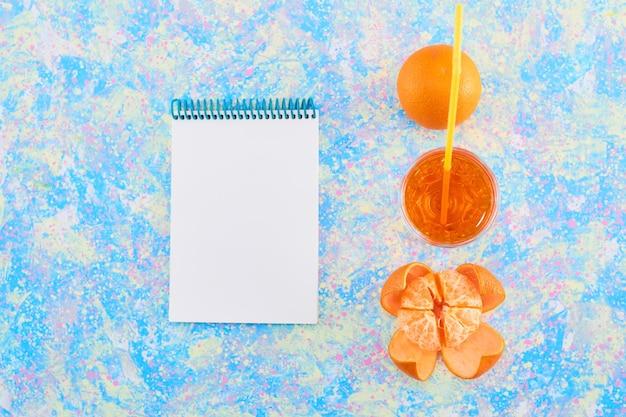 Un vaso de jugo de naranja con mandarinas alrededor sobre fondo azul con un cuaderno a un lado. foto de alta calidad