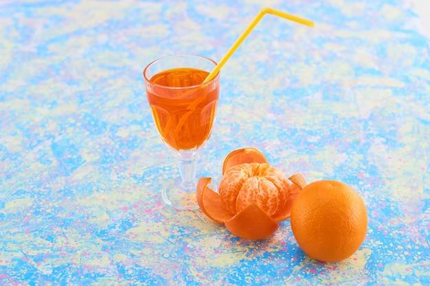 Un vaso de jugo de naranja con mandarinas alrededor sobre fondo azul. foto de alta calidad