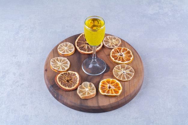 Un vaso de jugo, naranja seca y rodajas de limón a bordo, sobre el fondo de mármol.