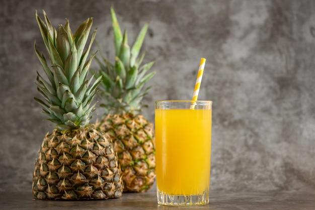 Vaso de jugo de piña con frutas frescas en fundamento gris.