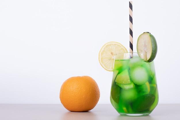 Un vaso de jugo con rodajas de frutas y mandarina.