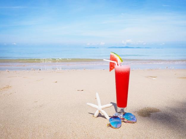 Vaso de jugo de sandía en la playa de verano
