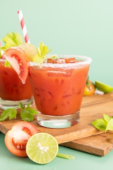 Vaso de jugo de tomate, limón con manojo brillante fresco de tomates aislado sobre fondo verde, perejil verde. bebida vegetal.