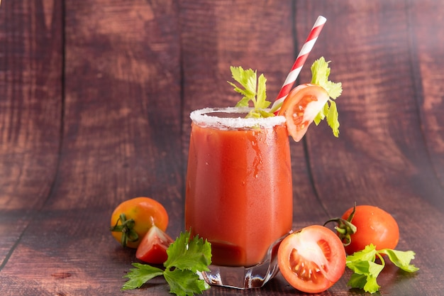 Vaso de jugo de tomate con tomates frescos brillantes, perejil verde sobre un fondo oscuro. bebida vegetal.