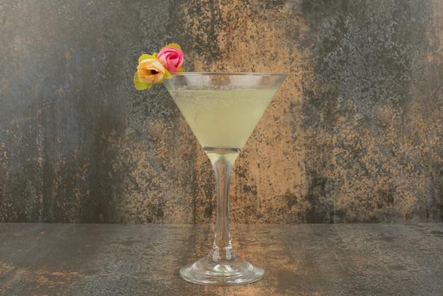 Un vaso de jugosa limonada y rosas sobre la superficie de mármol.
