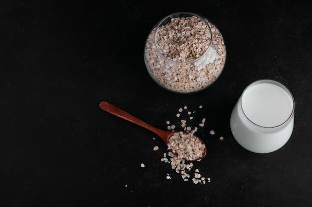 Un vaso de leche acompañado de una taza de cereales.