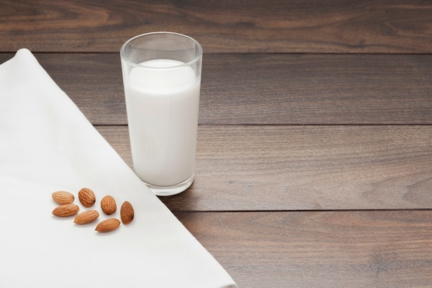 Vaso de leche de almendras sobre fondo de madera