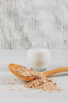 Vaso de leche con avena en cuchara de madera vista lateral sobre un fondo blanco de madera