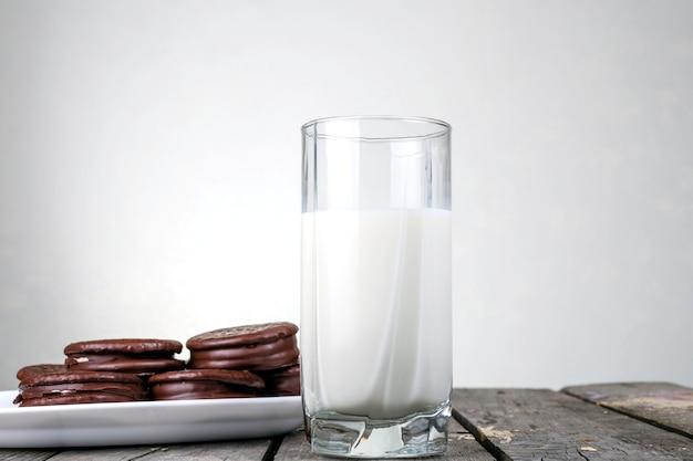 Vaso de leche en el centro sobre una mesa de madera y galletas con glaseado de chocolate en una placa blanca.
