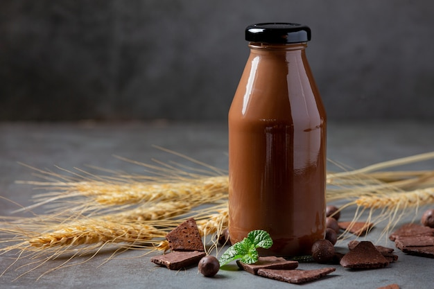Vaso de leche con chocolate en la superficie oscura.