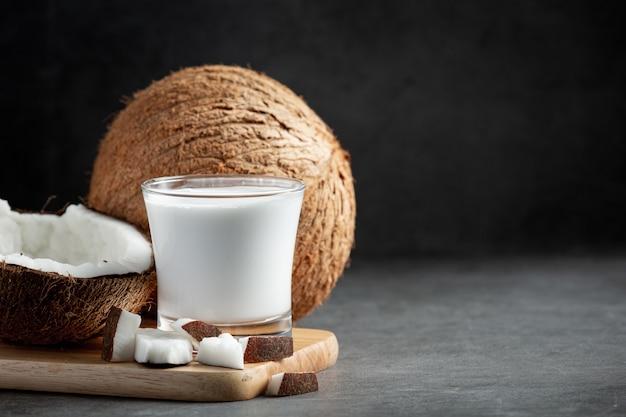 Vaso de leche de coco en tabla de cortar de madera
