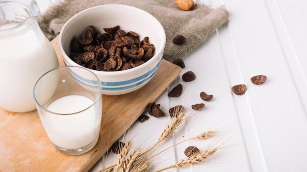 Vaso de leche y copos de chocolate seco en la mesa