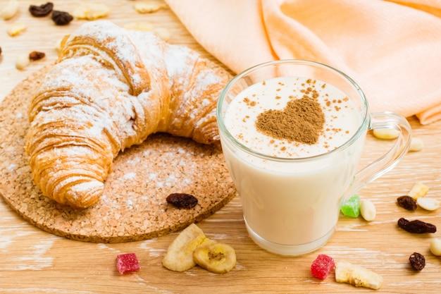 Vaso de leche con corazón de canela y croissant en azúcar en polvo sobre una mesa de madera