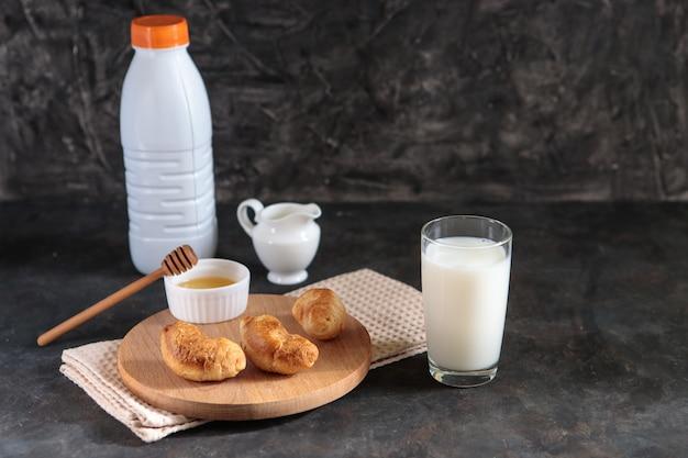 Vaso con leche y cruasanes con miel sobre un fondo negro. sabroso desayuno francés. postre. espacio para texto