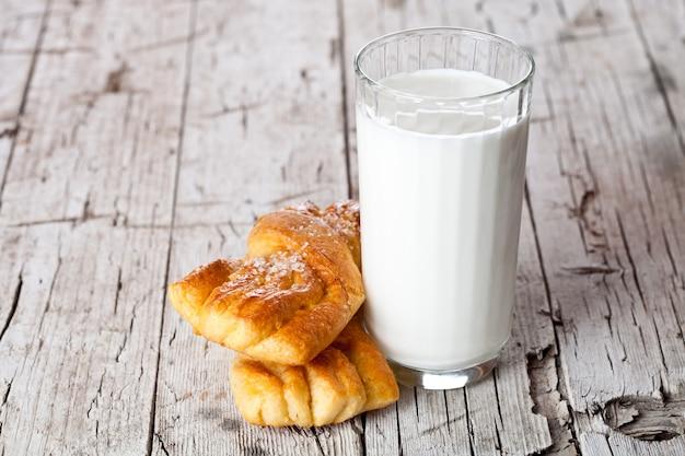 Vaso de leche y dos bollos recién horneados.