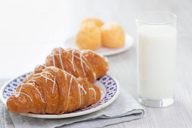 Vaso de leche y dos croissants.