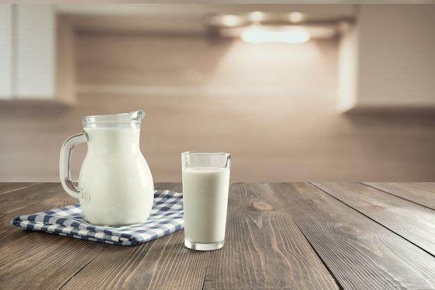 Vaso de leche fresca y jarra sobre mesa de madera con desenfoque de cocina como fondo.