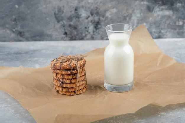 Vaso de leche fresca y pila de deliciosas galletas en hoja de papel.