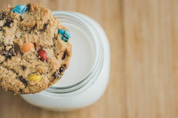Vaso de leche y galletas de azúcar caseras con coloridos dulces de chocolate sobre una plancha de madera. copia espacio vista superior.