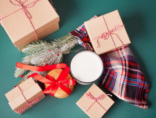 Vaso de leche, galletas, cajas de regalo y rama de pino en la mesa verde. navidad.