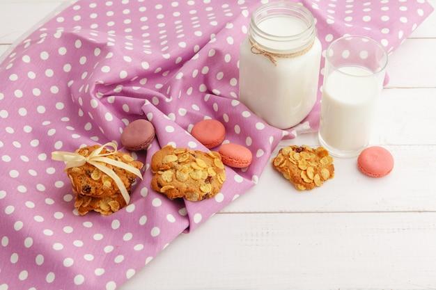 Vaso de leche y galletas galletas con paño de cocina sobre fondo claro
