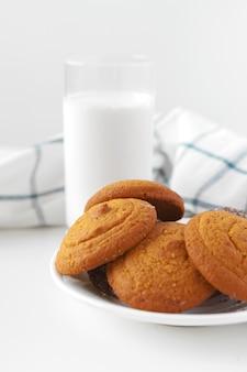 Vaso de leche y galletas con paño de cocina en la pared de luz