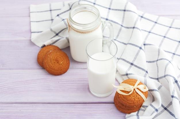 Vaso de leche y galletas con paño de cocina sobre fondo claro