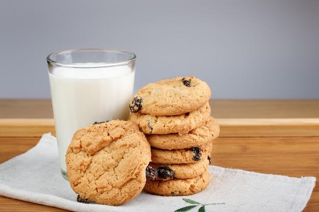 Un vaso de leche y galletas con pasas en una mesa de madera
