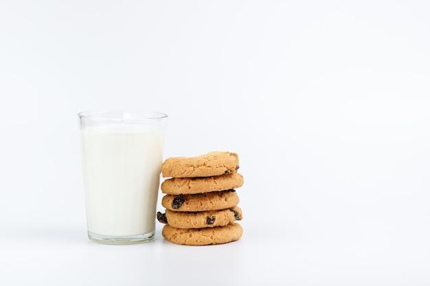 Un vaso de leche y galletas sobre un fondo blanco.
