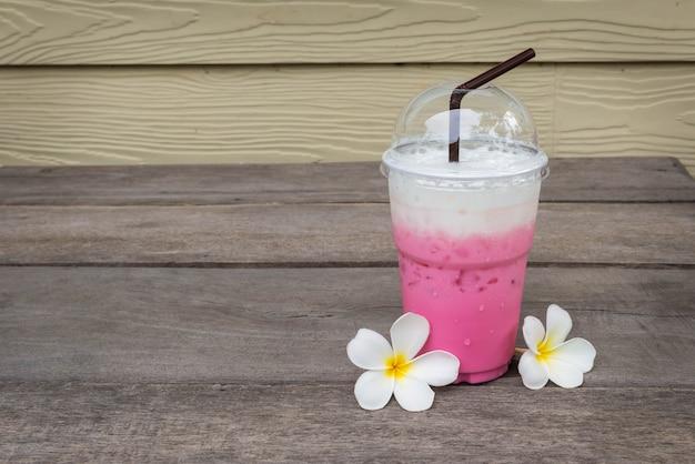 Vaso de leche de hielo rosa cerca de champaka chite en la mesa de madera en la cafetería